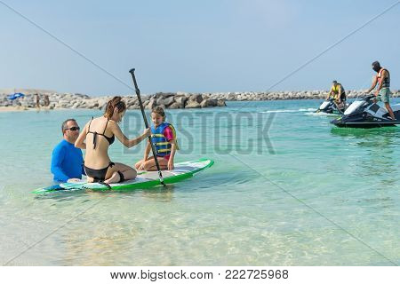 Mother and his adorable little daughter sitting on stand up board having fun during summer beach vacation. Little girl with his father learning surfing.