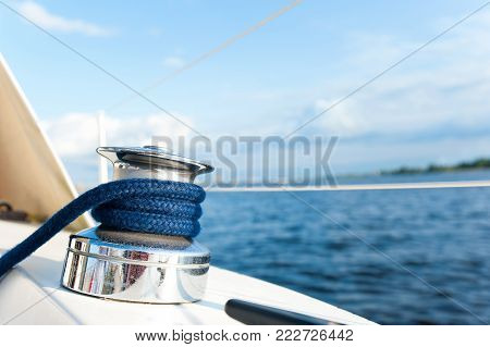Shiny yacht tackle during the ocean voyage. Winch on a sailboat as sailing concept. Outdoors horizontal colored closeup image