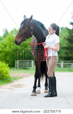 Young teenage lady leads and tenderly looking at her favorite bay horse. Vibrant colored outdoors vertical summertime image.