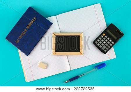 A blue book with an inscription in Russian - a student's record book. Pen, calculator and blank notebooks on a blue background. Students' Day. Copy space