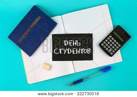 A blue book with an inscription in Russian - a student's record book. Pen, calculator and blank notebooks on a blue background. Inscription in Russian - Students Day