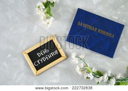 A blue book with an inscription in Russian - a student's record book. White flowers on a gray background. Inscription in Russian - Students Day. Tatyana's Day