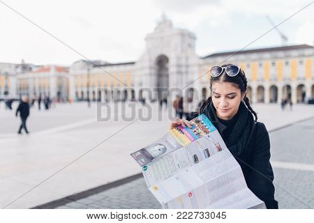 Happy female traveler on a trip around Europe.Female tourist holding a map in her hands,getting around the capital of Portugal.Smiling woman standing on a main square of Lisbon.Exploring new cultures