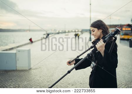 Young enthusiastic female photographer setting up lightweight carbon travel tripod for sunset/sunrise log exposure still shot.Stabilized photography and video.Equipment for outdoor landscape filming.