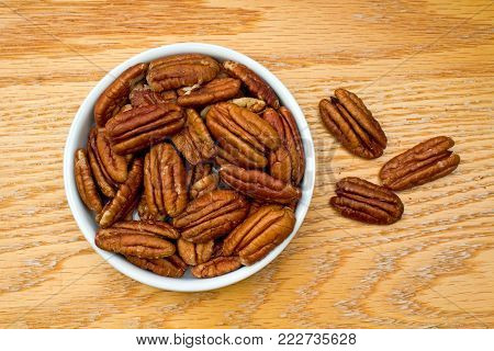 White Bowl Full of Healthy Pecans on an oak table
