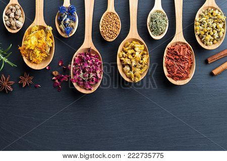 Herbs on spoons on a wooden background with copy space, top view. Nasturtium seeds, calendula, cornflower, rose petals, fenugreek seeds, mullein, horsetail, sandalwood, chamomile.