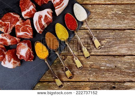 Perfect Raw Pork Neck with spoons with different spices Wooden Cutting Board. Top View