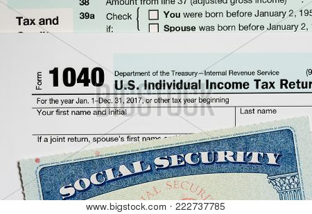Social Security card in the USA laid on top of Form 1040 tax return of income in retirement