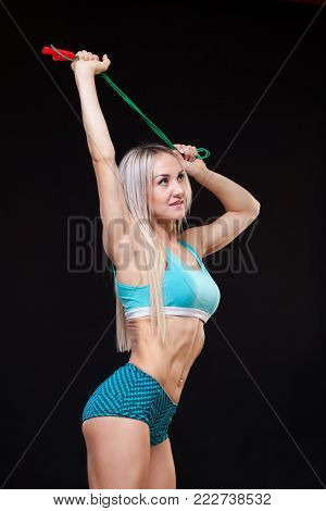 Sport, activity. Cute woman with skipping rope. Muscular woman black background