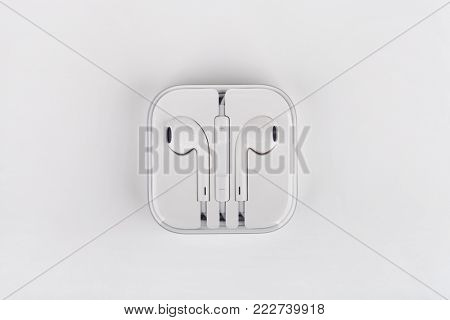 White headphones for smartphone in transparent box with shadow