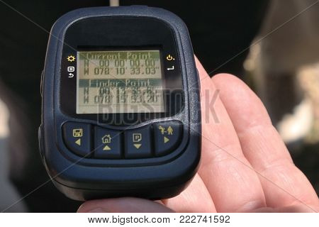 Hand holds a GPS logger with the coordinates of the Equator Zero Line in Ecuador, close-up picture