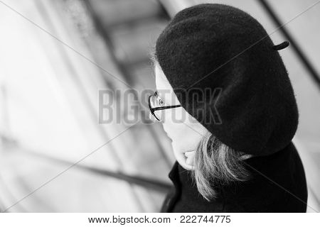 STRASBOURG, FRANCE - DEC 23, 2016: Woman wearing French beret and Cacharel fashionable eyewear - black and white image