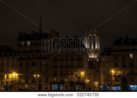 Notre Dame de Paris cathedral surrounded by medieval residential buildings typical from Ile de la Cite in Paris, France, during an winter evening, taken from the quays of Seine river