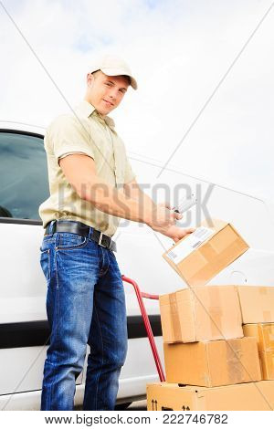 a delivery person is standing next to his white van, scanning the barcode on a parcel. all barcodes on the parcels are generated by myself and contain no useful data.