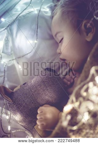 Cute little baby sleeping at home in his bed with his best friend, soft toy dog, vintage style photo with glowing lights, childhood dreams
