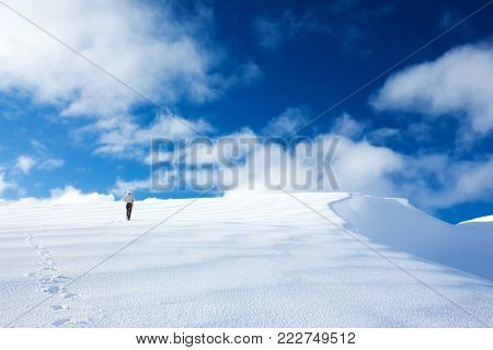 Woman traveling in the mountains in wintertime, active sportive lifestyle, walking along beautiful white snow, happy winter holidays