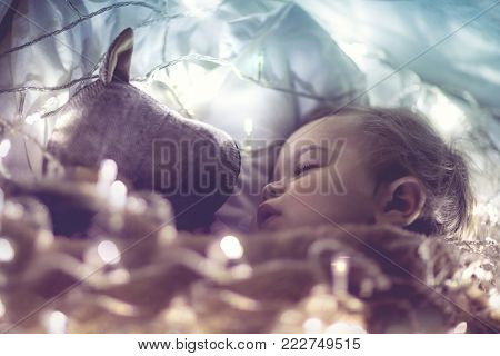 Sweet little baby boy sleeping with favourite soft toy, dreaming at home on magic night, vintage style fantasy photo