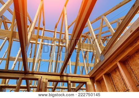 Close-up of gables roof on stick built home under construction and blue sky New build roof with wooden truss, post and beam framework. Timber frame house, real estate background
