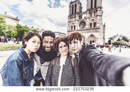 Multi-ethnic group of friends having fun in Paris, taking a selfie in front of the Notre Dame Cathedral.