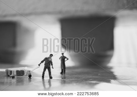 Miniature people, worker and employer at work site, using for logistic and business concept - Black and white filter