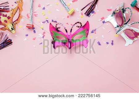 Table top view aerial image of beautiful colorful carnival mask or photo booth prop background.Flat lay object on modern rustic pink wallpaper at  office desk studio.space for creative design mock up.