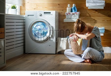 tired  housewife woman in stress sleeps in laundry room with washing machine