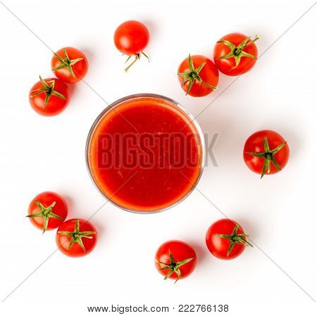 Tomato juice in glass and tomatoes on a white background. The view from the top.