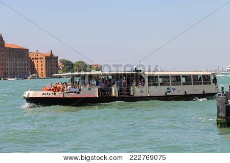 Venice, Italy - August 13, 2016: Passengers boats with tourists in the Giudecca Canal