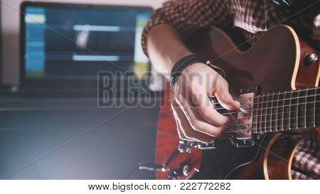 Young musician composes and records soundtrack playing the guitar, using computer and keyboard, from the front view