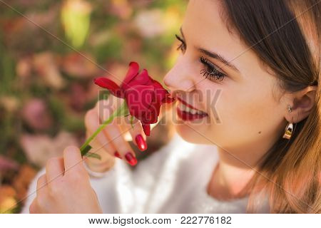 An Happy Girl sniffing a red rose