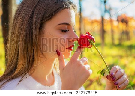 A Girl with closed eyes sniffing a red rose