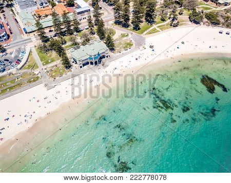 Aerial photograph over a busy Cottesloe Beach, Perth, Western Australia, on a clear summer afternoon.