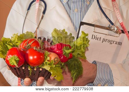 Close-up of male nutritionist hands measuring vegetables with tape. Portrait Of Male Dietician With Fresh Vegetables And Diary. Healthy, Diet concept