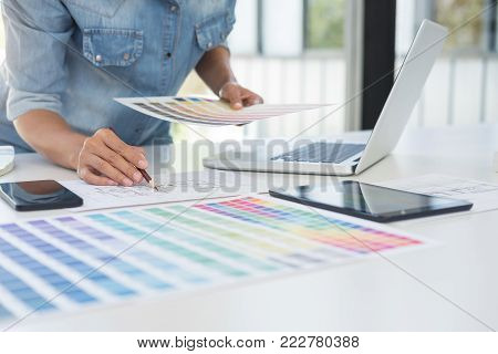 Color samples, colour chart, swatch sample, Graphic designer being selecting Color table and graphics tablet, pen at workplace with work example on wooden desk.