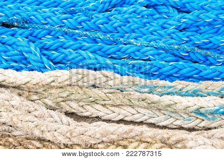 Blue and white nautical rope texture. Naval tackle closeup photo. Summer cruise travel banner. Navy blue and white cordage top view. Seaside pier texture. Yacht sport equipment. Ship or boat cord