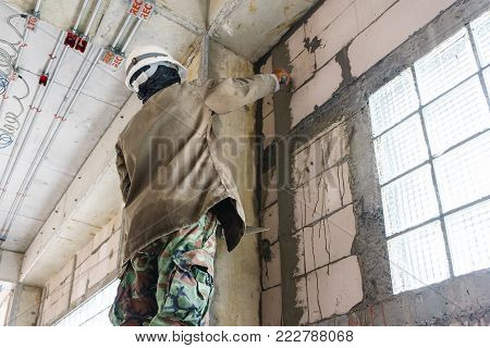 Construction worker with wall plastering tools renovating house. Plasterer renovating indoor walls and ceilings with float and plaster.