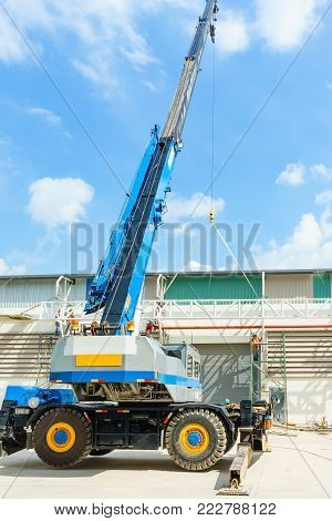 blue hydraulic truck crane standing on a construction site under construction. A worker is standing on a scissor lift at a suitable height to help positioning it.