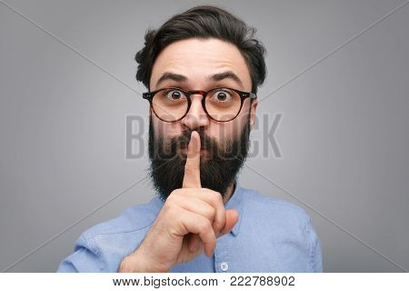 Bearded man in glasses gesturing silence with finger up to mouth on gray background.