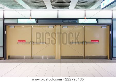 Emergency exit door with Exit Sign in underground passage of train subway