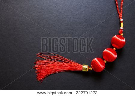 Chinese Lucky knot on black background. Chinese New Year decor top view photo. Red silk knot. Chinese Lunar New Year top view photo. Asian winter holiday greeting flat lay. Lunar New Year background