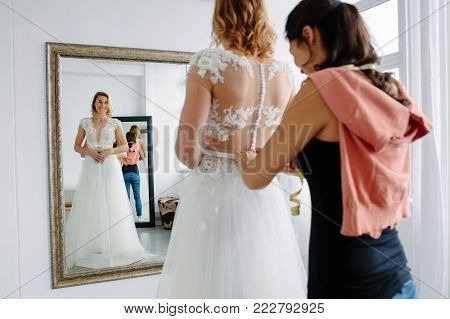 Female entrepreneur in bridal clothing store. Woman with a diary in her bridal boutique.