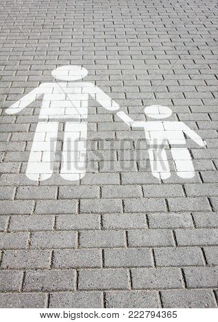 Sign pedestrian crossing painted on the road, safety of children - adult holds the child by the hand