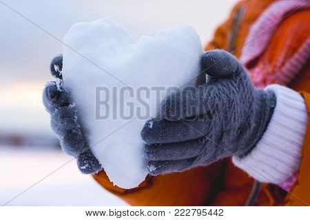 girl holding a heart of snow, wishes to congratulate her friend on Valentine's Day and wish her happiness and love