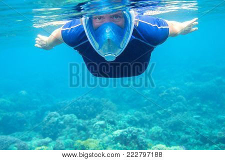 Woman swimming in turquoise blue sea water. Tropical sea background. Woman swims undersea in swimming costume and full-face mask. Underwater photo of female snorkel. Snorkeling in coral reef