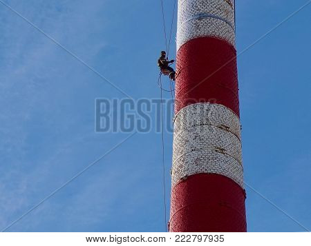 Industrial alpinism. Works at high altitude. Steeplejack. The man in the safety system, in the obvozke. Performs painting, work on a structure of great height. The building is red and white. Background blue sky.