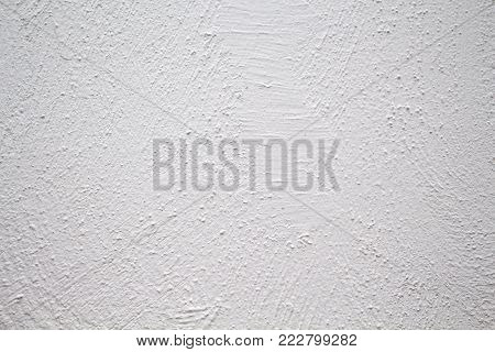Painted wall with rough texture closeup photo. White plaster with brushed texture. White house wall. Greek architecture background. Pottery house wall. White painted surface. Vintage or shabby chic