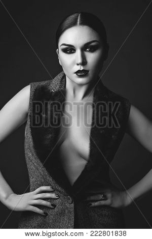 beautiful young woman with balck hair and dark  smokey eye makeup wearing vest with fur collar. studio beauty shot. copy space.