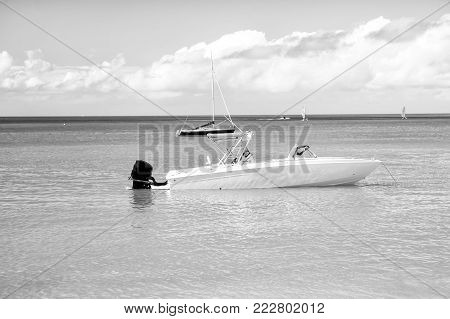 traveling and vacation, sport and sailing, man, yachtsman on motorboat, yacht on sea, ocean water, coast sunny summer outdoor on blue cloudy sky background in St. John, Antigua
