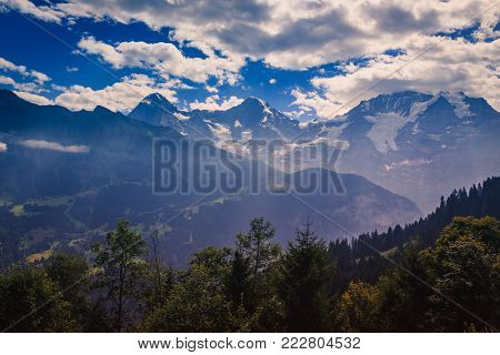 View on the Bernese alps from car-free village Murren on a cloudy day in summer. The majestic world famous trio Eiger - Monch & Jungfrau in the background. Bernese Oberland - Switzerland