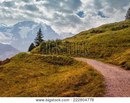 mountain path winds up from Grutschalp to Murren in the Bernese Alps. The famous Jungfrau in the background. Lauterbrunnen - Bernese Oberland - Switzerland